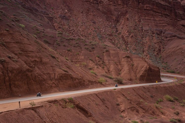 People riding motorcycles on road by mountain