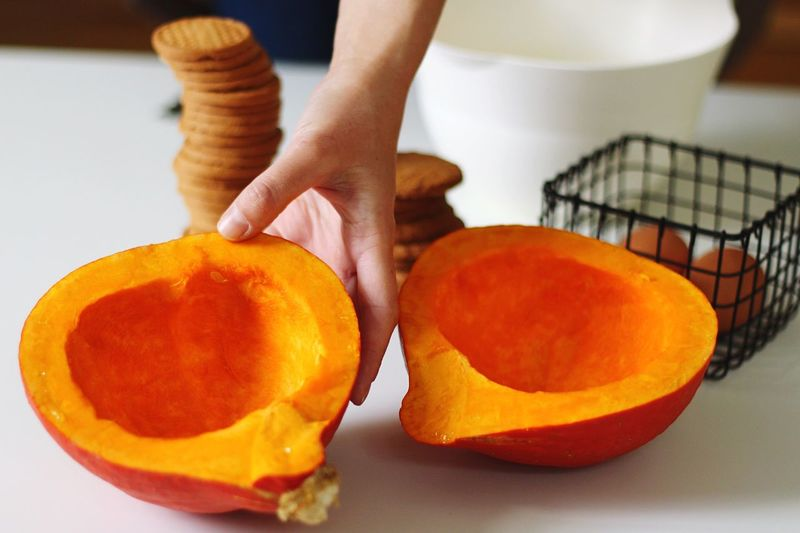 Cropped image of hand holding sliced pumpkin on table