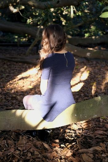 Rear View Of Woman Sitting On Tree Trunk