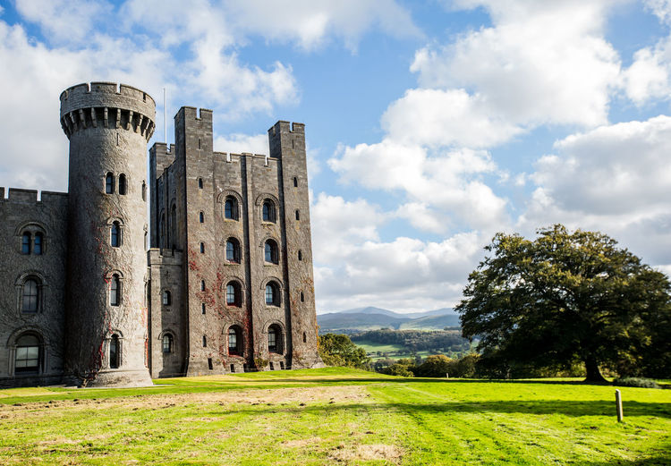 Penrhyn Castle in North Wales Sky Cloud - Sky Architecture Built Structure Plant Grass History Nature The Past Building Exterior Day Tree Land Field No People Green Color Landscape Ancient Building Environment Outdoors Ancient Civilization Ruined Penrhyn Castle Sunny Day