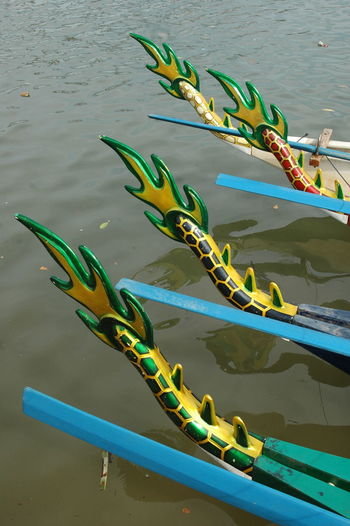 Artificial dragon tails on boats moored in river