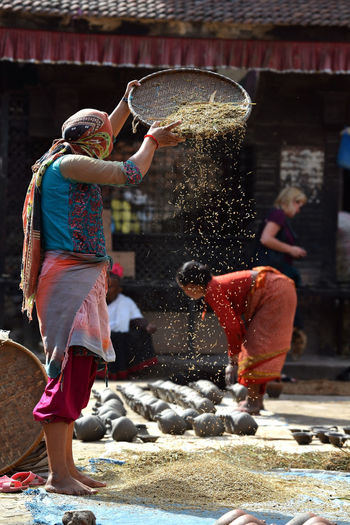 Unidentified woman threshing grain in traditional way in the Pottery square of Bhaktapur. The city is part of UNESCO heritage. On October 10, 2013 in Kathmandu, Nepal Bhaktapur,Nepal Cereal Farmer Kathmandu Nepal Nepalese Peasant Rice Sifting Woman Worker Working Bhaktapur Built Structure Cereal Plant Cultivate Grain Lifestyles Pottery Square Produce Real People Shovel Threshing Traditional Woman Working