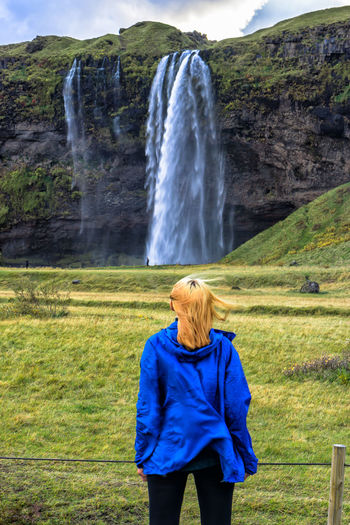 Adult Beauty In Nature Blond Hair Day Grass Green Color Long Exposure Motion Nature One Person Outdoors People Rear View Scenics Standing Water Waterfall Waiting Game