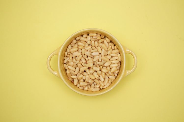pignoli in a yellow bowl on yellow background Bowl Colored Background Directly Above Food Healthy Eating No People Pignolo Raw Food Studio Shot Yellow Background