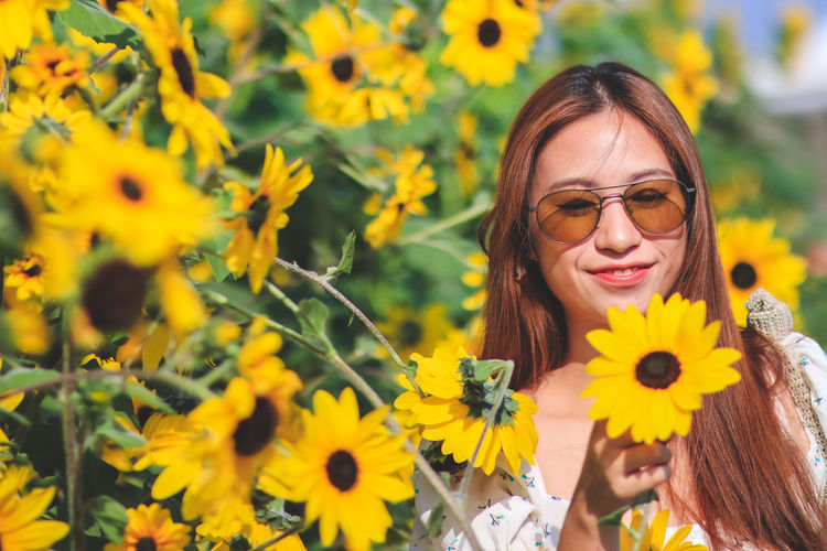 Portrait of smiling woman with yellow flowers