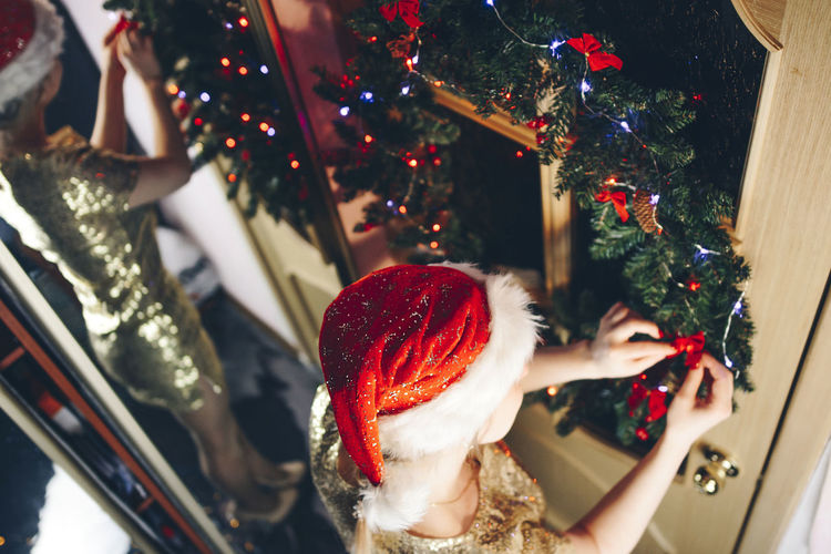 Girl decorates the door of the house on Christmas day Christmas Celebration Holiday christmas tree Real People Decoration Tree Lifestyles Christmas Decoration Indoors  Christmas Ornament Red Women Girl Santa Hat Reflection Bokeh Lights Legs International Women's Day 2019