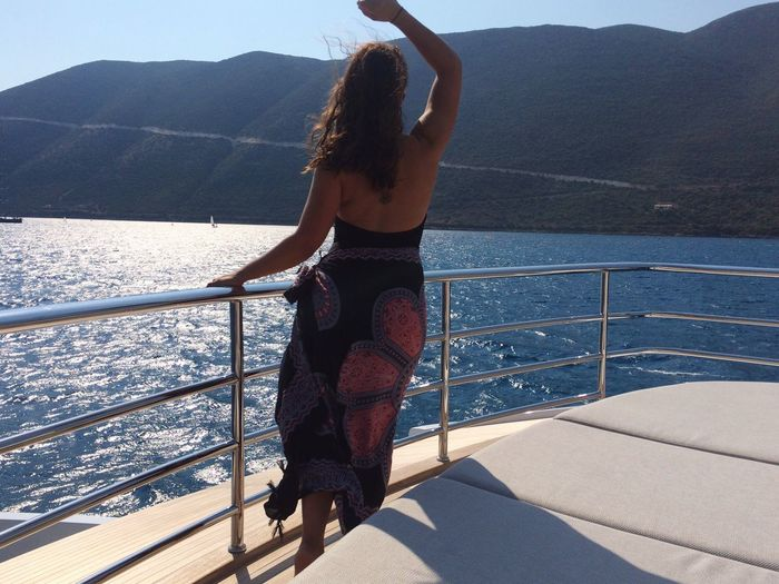 Young woman standing on boat sailing in sea