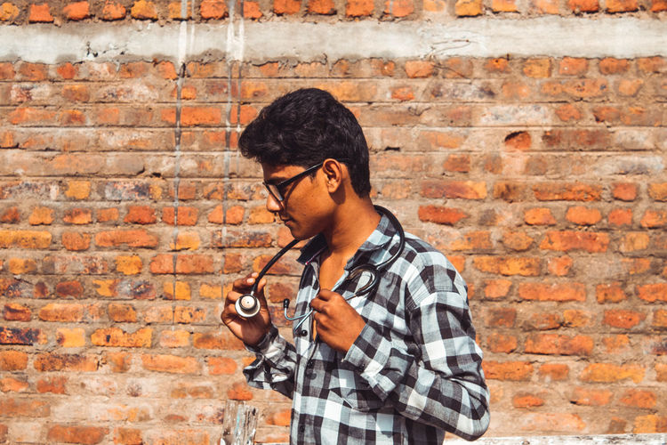 Man with stethoscope standing against brick wall