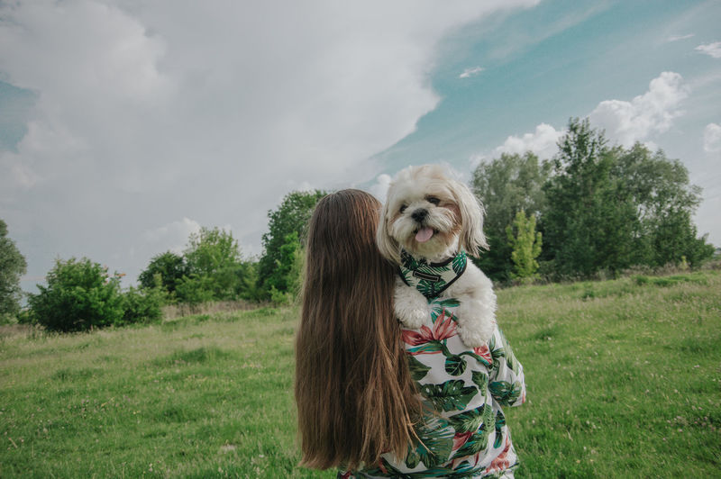 A girl with long hair carrying little dog shih tzu in her arms