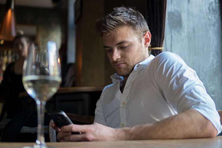 Tinder Refreshment Food And Drink Waiting Smart Phone Bar - Drink Establishment Bar Counter Looking Drinking Wineglass Headshot Portrait Alcohol Holding Glass Restaurant Happy Hour Business Bad Habit Date Night - Romance