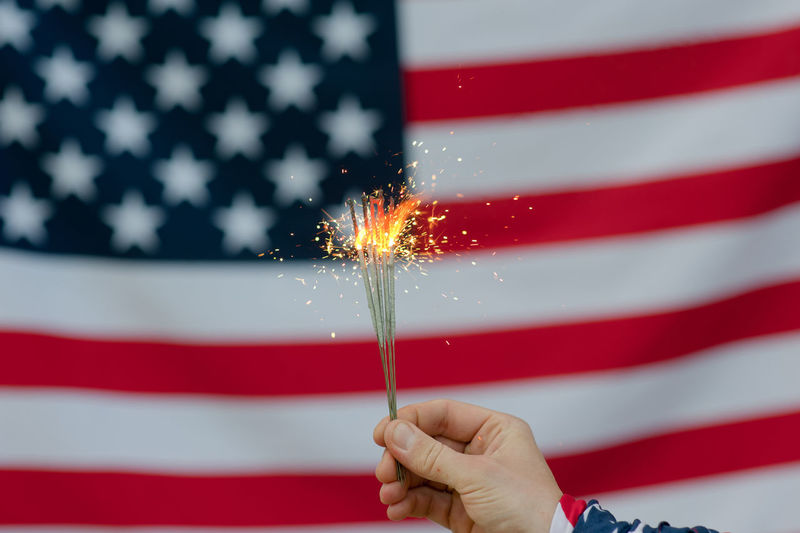 USA flag Red Holding Celebration Human Hand Sparkler Hand Patriotism One Person Motion Flag Human Body Part Firework Event Burning Sparks Real People Firework - Man Made Object Firework Display Finger