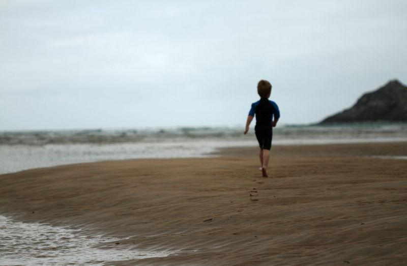 Rear View Of Boy Running At Beach