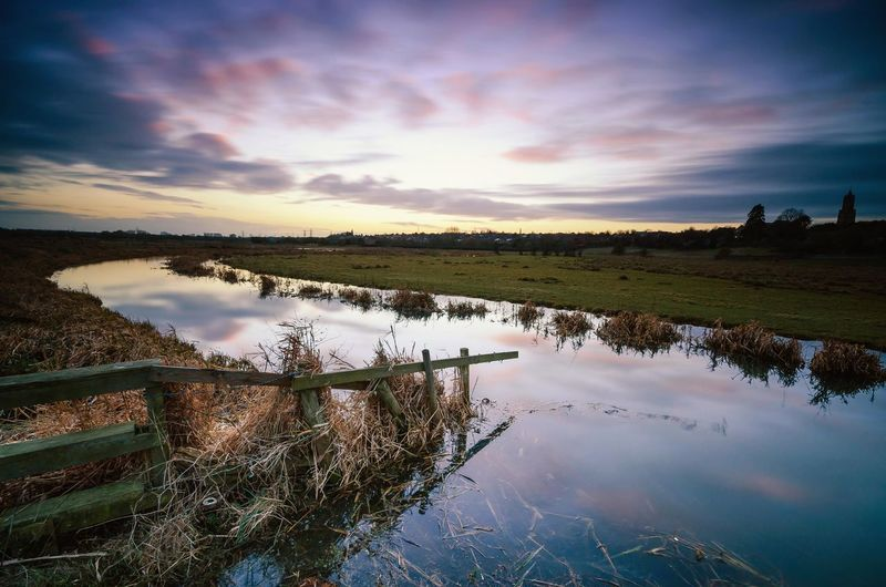 View Of Irrigation Canal On Field Against Sky During Sunset