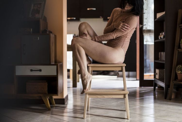Low section of seductive young woman sitting on stool at home