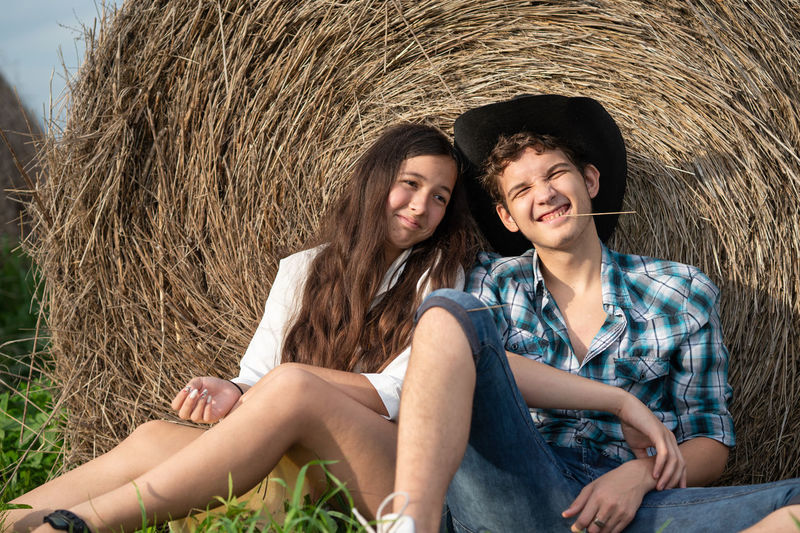 Portrait of a smiling young couple sitting outdoors