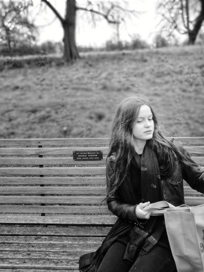 Woman With Bag Sitting On Bench