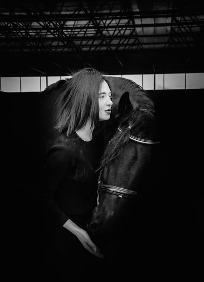 Side view of woman standing with horse in darkroom