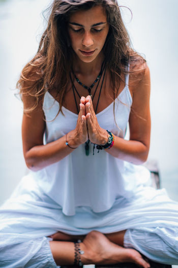 Mindfulness and Meditation. Yoga Woman. Hands in Prayer Position. Meditate Yoga Prayer Nature Water Lake Woman Hands Meditation Lifestyle People Relaxation Mindfulness Young Exercise Healthy Beautiful Asana Balance Outdoor Sitting Pose Relax Female Beauty Concentration Life Meditating Tranquility Health Natural Spirituality Inner Peace Outdoors Practice Landscape Peace Zen Harmony Leisure Peaceful Vitality Calm One Person Long Hair Beautiful Woman