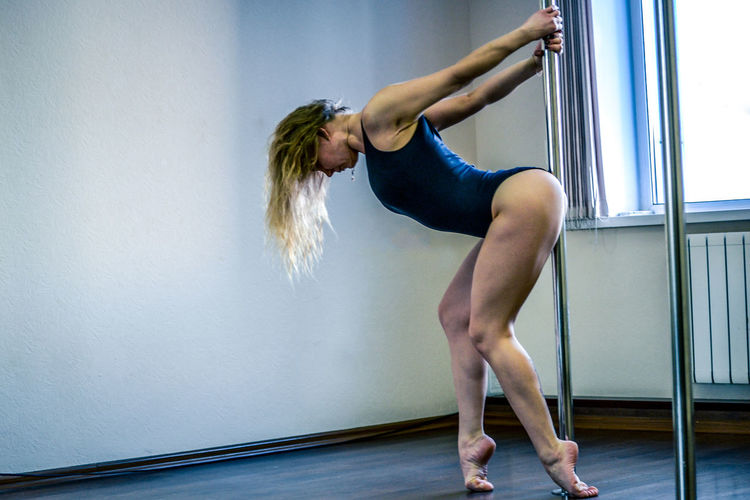 Sensual woman pole dancing against wall