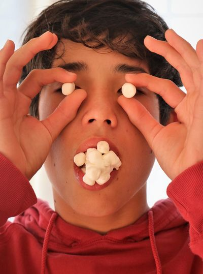 Close-up portrait of child eating marshmallows