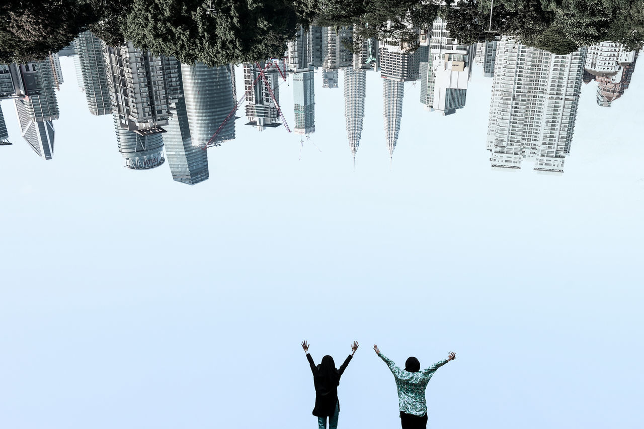 View of two people in city against clear sky