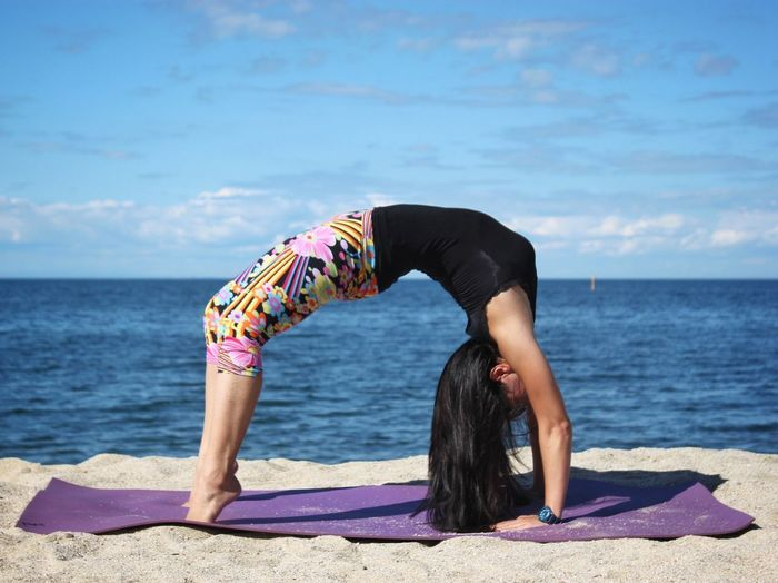 Full Length Of Woman Practicing Wheel Pose On Beach