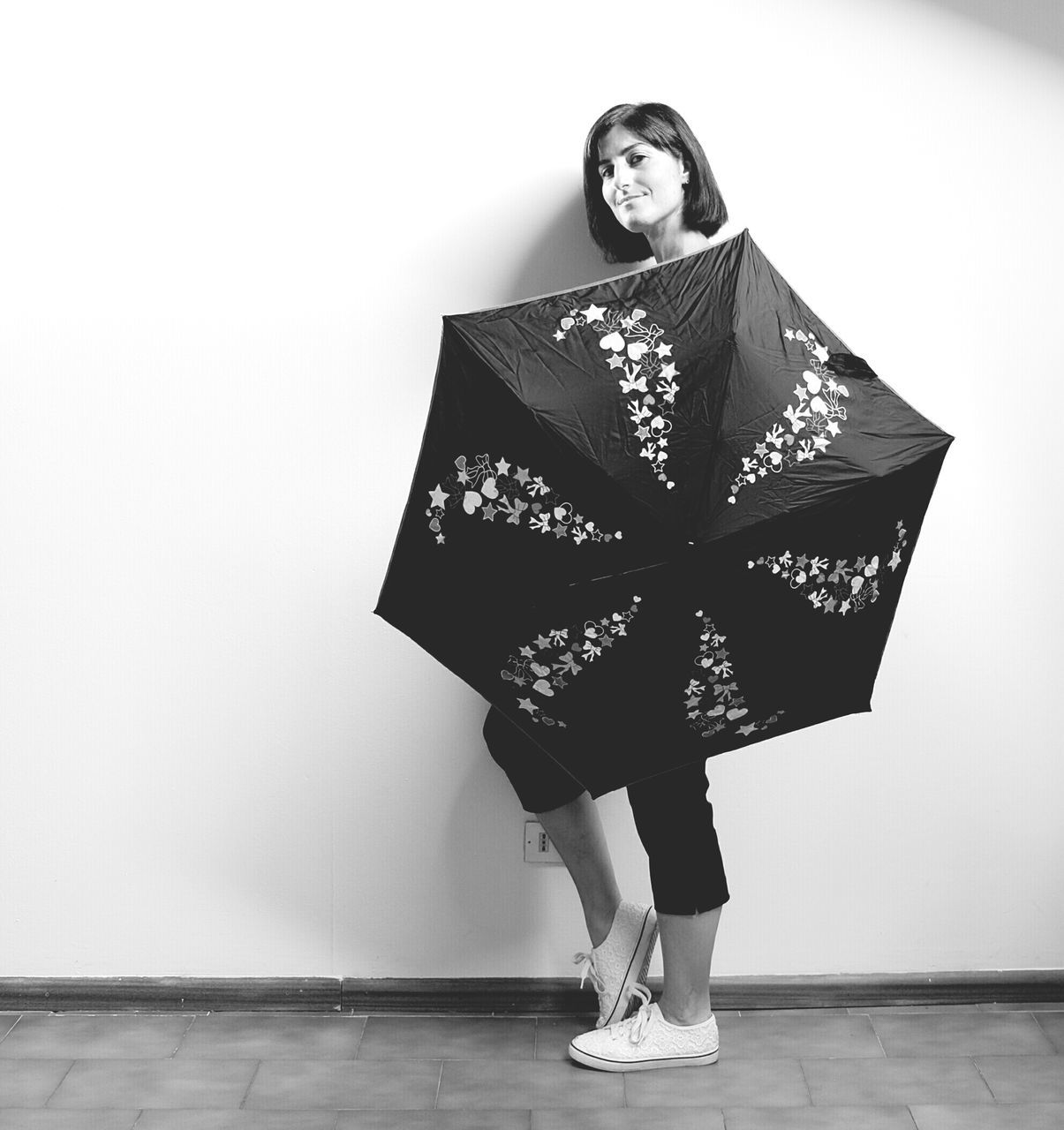 Full Length Of Woman Holding Umbrella While Standing By Wall