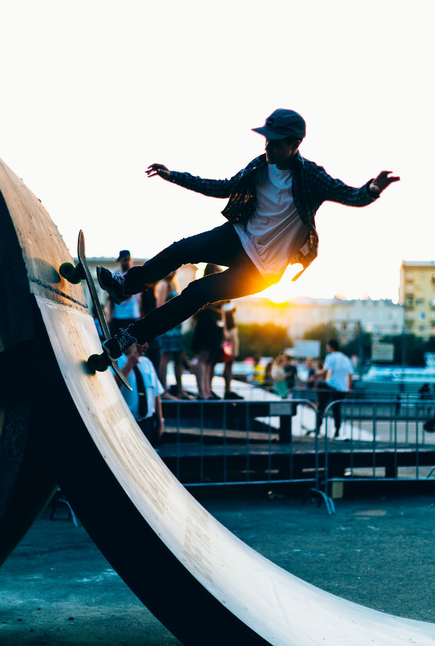 full length, mid-air, leisure activity, real people, jumping, fun, motion, vitality, enjoyment, energetic, outdoors, day, lifestyles, built structure, clear sky, one person, building exterior, architecture, stunt, young adult, people