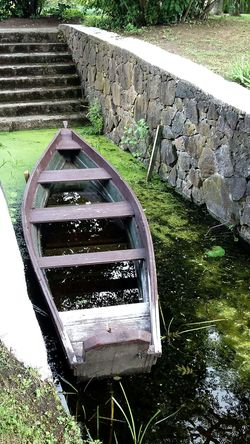 Boat in park pond Water Tranquility Tranquil Scene Scenics No People Outdoors Nature Day Beauty In Nature Pond Pond Life Pond Plants Sunlight Green Lake Boat Old Boat Stairs Stairs_collection Stonesteps Stone Wall, Stones, Scum Scum Pond Dark Water Water Reflections Water In Boat