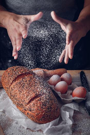 Baker's man spraying flour on bread and eggs