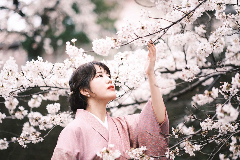 Portrait of young woman with pink cherry blossoms in spring