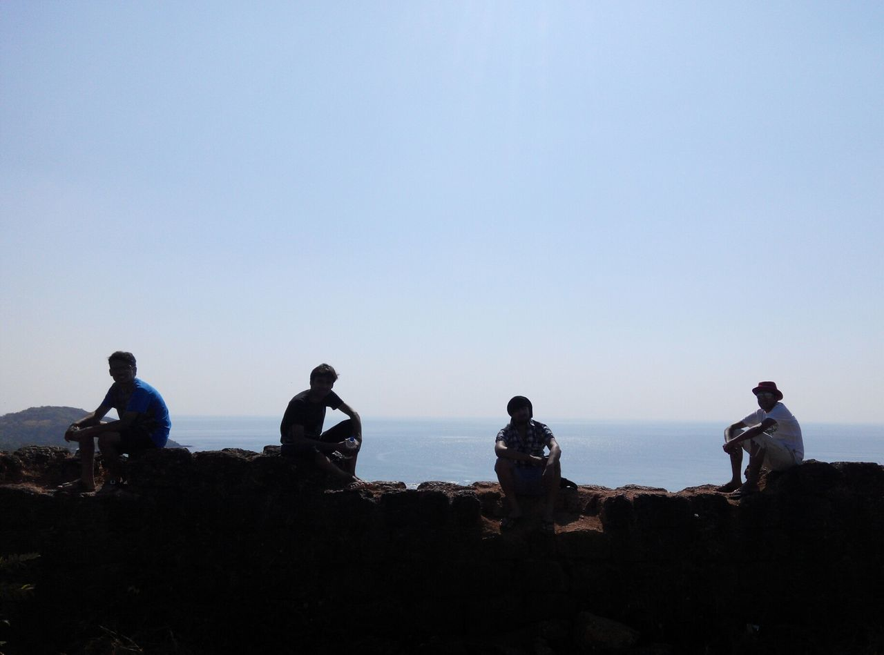 clear sky, copy space, men, silhouette, togetherness, blue, nature, outdoors, leisure activity, day, sky, sea, real people, sitting, horizon over water, water, beauty in nature, people