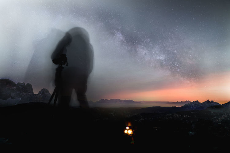 Multiple image of silhouette man standing on land against sky at night