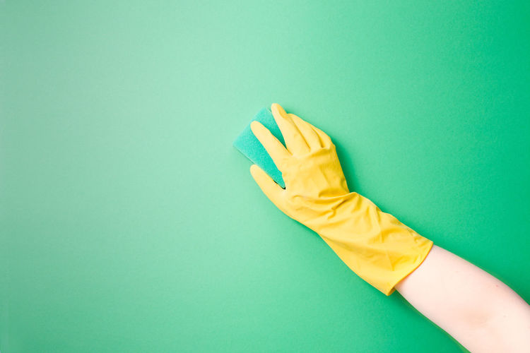 A female hand in a yellow rubber glove washes a plain surface with a green paralon sponge