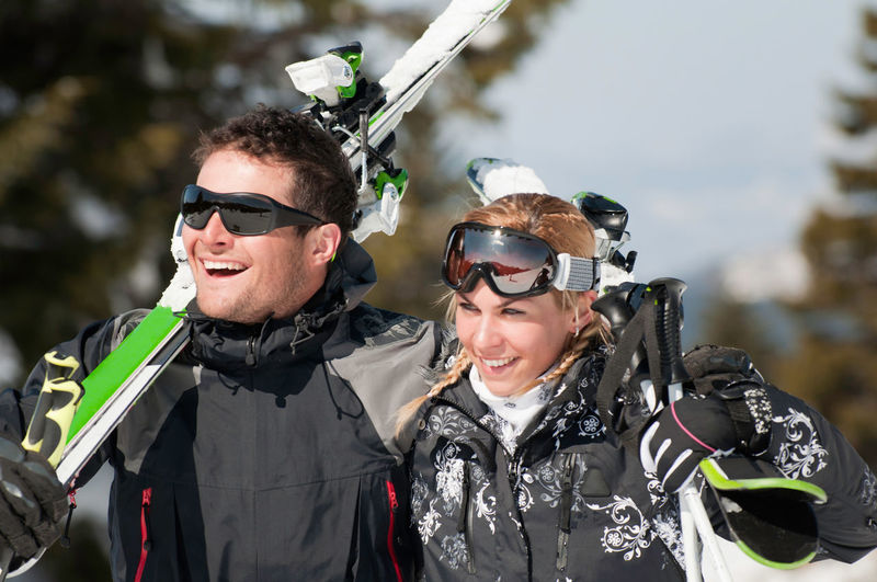 Happy Mid Adult Couple With Snowboards Looking Away