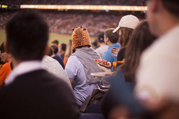 Man with giraffe hat on stadium