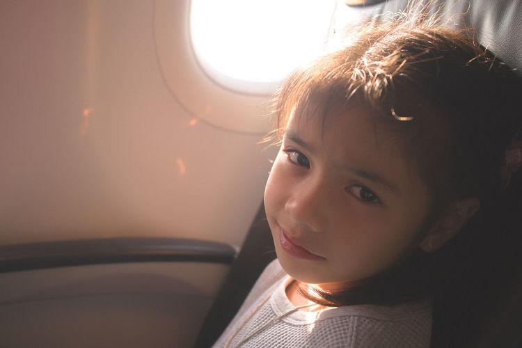Portrait of boy looking through airplane window