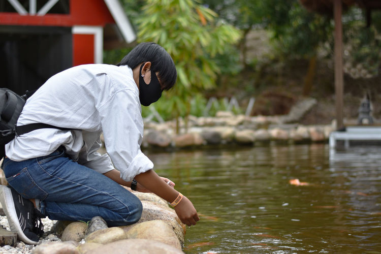 Side view of man sitting on rock by lake