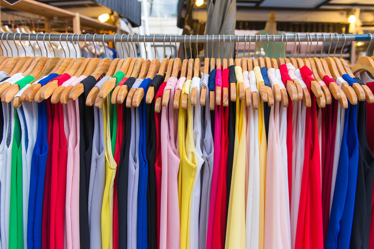 Multi colored dresses hanging in rack at store