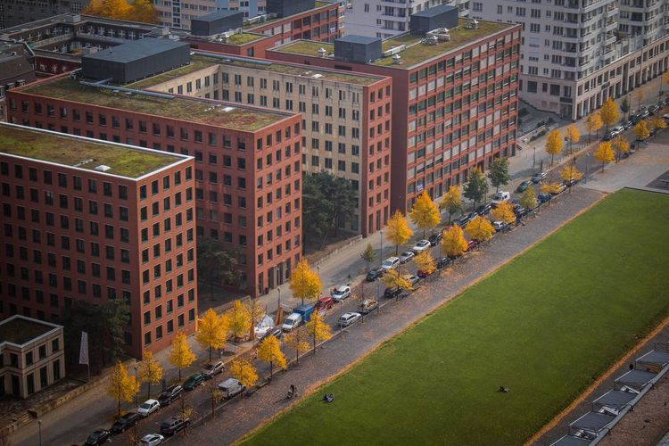 High angle view of cars by buildings in city during autumn