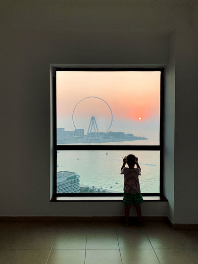 Little boy silhouette looking outside at scenic marine view with dubai eye at sunset