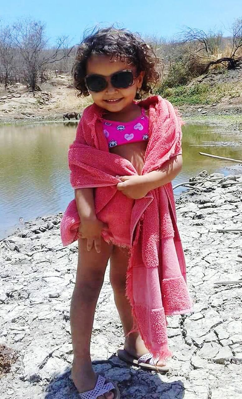 childhood, sunglasses, full length, one person, water, looking at camera, portrait, elementary age, girls, outdoors, one girl only, day, leisure activity, children only, smiling, real people, child, lake, cute, happiness, beach, standing, nature, tree, sky, people