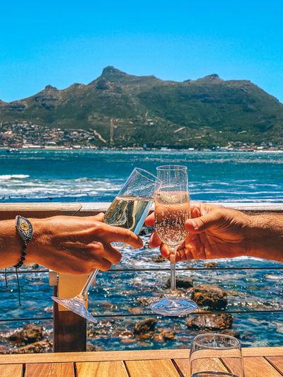 Close-up of wine glass against calm sea