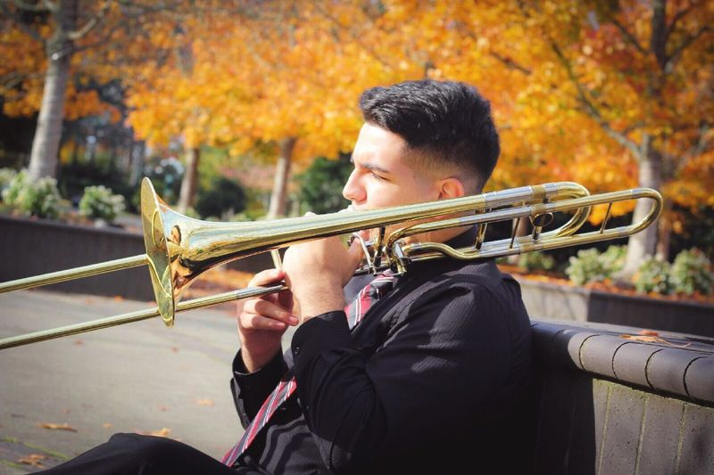 Young Man Playing Trumpet While Sitting In Park During Autumn