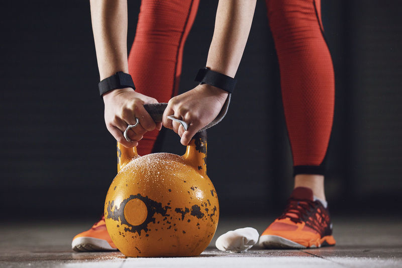 Low Section Of Woman Holding Kettlebell On Floor