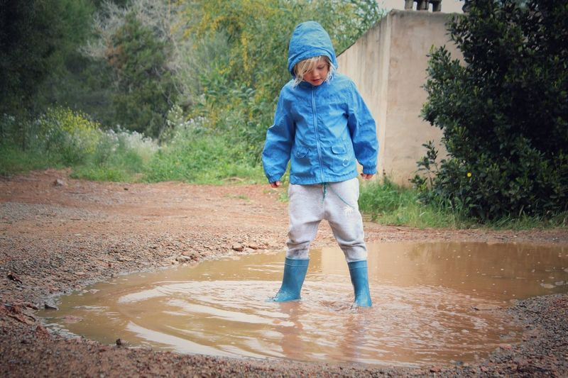 Full Length Of Child Standing In Puddle