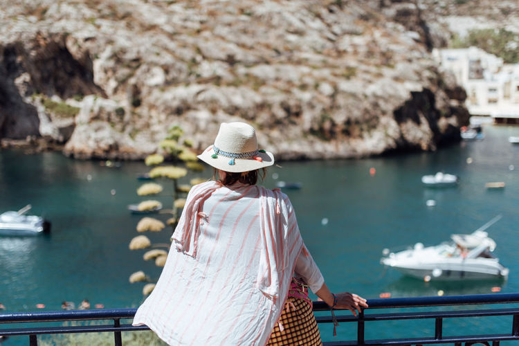 Rear view of woman looking at sea while standing by railing