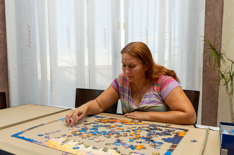 Mature woman playing with puzzle at home