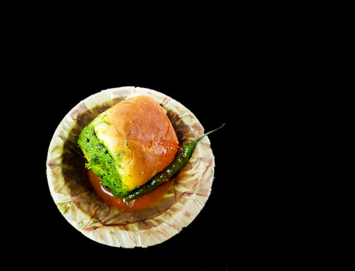 Vada pau bread and green sauce on a plate Chilling Fast Food Green Hanging Out Isolated Mumbai Potato Pudina Street Food Worldwide Bread Chilli Chutney Close-up Dark Background Food Food And Drink Freshness Paprika, Red, Green, Vegetable, Chilli, Ready-to-eat Snow Vadapau