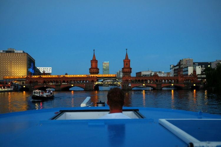 Rear View Of Man In Boat By Oberbaum Bridge Over River Spree Against Clear Sky At Dusk